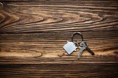 Symbole de maison avec la clé argentée sur le fond en bois Photo libre de droits