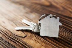 Symbole de maison avec la clé argentée sur le fond en bois Photo stock