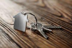 Symbole de maison avec la clé argentée sur le fond en bois Photos stock