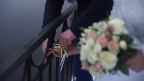 Symbole de mariage, serrure dans des mains des jeunes mariés Les nouveaux mariés fixent la serrure sur le pont comme symbole de l Photos libres de droits