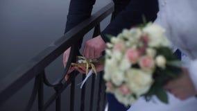 Symbole de mariage, serrure dans des mains des jeunes mariés Les nouveaux mariés fixent la serrure sur le pont comme symbole de l Image stock