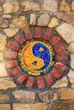 Symbole de mosaïque de Yin et de yang sur le mur en pierre image stock