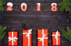 Symbole de signe de la bonne année 2018 des biscuits rouges et blancs de pain d'épice sur le fond en bois foncé avec les boîte-ca Photographie stock libre de droits