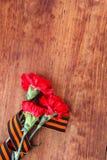 Symbole des Sieges in der großer patriotischer Rotblume des Krieges drei und in George-Band auf Holztisch Stockfotografie