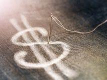 Symbole dollar tiré dans la craie dans les jeans, une aiguille et le fil Photo stock