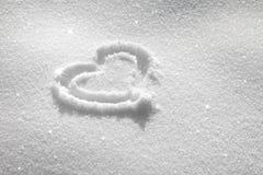 Symbole ensoleillé de coeur dans la neige fraîche Photos libres de droits