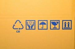 Symbole fragile bleu sur le carton Image stock