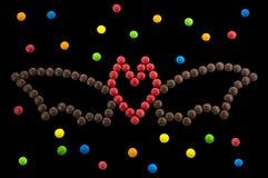 Symbole Halloween - une batte hors des sucreries rondes d'isolement image stock