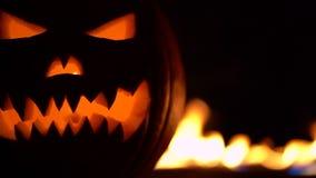 Symbole horrible de Halloween - Jack-o-lanterne Le chef effrayant du potiron en feu d'enfer flambe Moitié de courge orange sur banque de vidéos