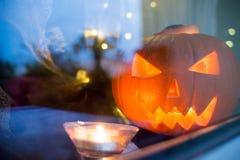 Symbole lumineux de pupkin de Halloween derrière la fenêtre à la maison avec les reflectons légers Photographie stock