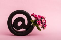 Symbole noir décoratif d'email sur le fond rose Images stock