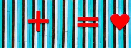 Symbole plus et égal et de coeur sur le mur en bois Photos stock