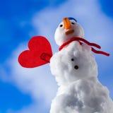 Symbole rouge d'amour de coeur de petit bonhomme de neige heureux extérieur. Hiver. Photographie stock