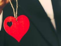 Symbole rouge d'amour de coeur sur le fond masculin de costume Photo stock