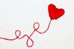 Symbole rouge de forme de coeur fait à partir de la laine d'isolement sur le blanc Images libres de droits