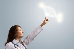 Symbole rougeoyant d'ADN de doigt de docteur de jeune femme Photographie stock