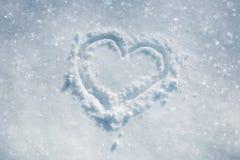 Symbole tiré par la main de coeur dans la neige aux chutes de neige Photographie stock libre de droits
