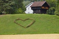 Symbole traditionnel norvégien de maison et de coeur de ferme dans le pays Images stock