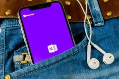 Symbolen för den Microsoft OneNote kontorsapplikationen på skärmen för Apple iPhone X i jeans stoppa i fickan Microsoft en anmärk arkivbilder