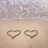 Symbolen van twee die harten op zand worden getrokken stock afbeelding