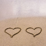 Symbolen van twee die harten op zand worden getrokken stock afbeeldingen