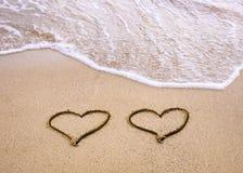 Symbolen van twee harten die op zand worden getrokken Stock Afbeeldingen