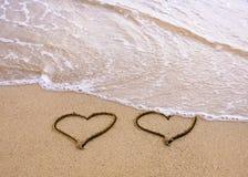 Symbolen van twee harten die op zand worden getrokken royalty-vrije stock foto