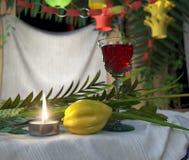 Symboler av den judiska ferien Sukkot med stearinljus- och vinexponeringsglas Arkivbild