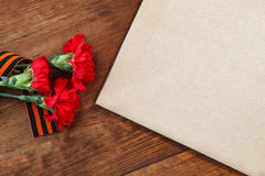Symboler av segern i stora patriotiska blomma och papper för krig tre röd på en tabell Bild för selektiv fokus Royaltyfri Fotografi
