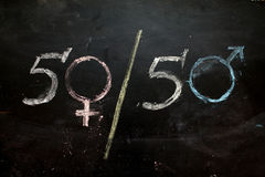 Symboler eller tecknet för mannen och kvinnligt för genus könsbestämmer utdraget på en svart tavla Royaltyfri Bild