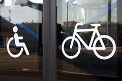 Symboler för den rörelsehindrade personen och cykeln på exponeringsglasbussdörrar, närbild fotografering för bildbyråer