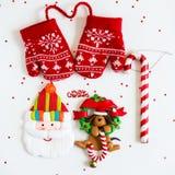 Symboler för glad jul - bokstäver, röda stack tumvanten, jultomten, D Royaltyfria Bilder