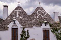 Symboler på de koniska taken av Alberobello i Italien Arkivbild