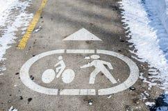Symboler som målas på asfalt av en gångare och en cykelbana Arkivfoto