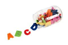 Symboles colorés d'alphabet dans la boîte en verre. Concept d'éducation. Image stock