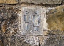Symboles d'homme et de femme sur le mur en pierre Photographie stock libre de droits