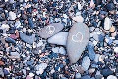 Symboles de paix et d'amour sur des roches Photos stock