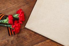 Symboles de victoire en grands fleur et papier patriotiques de rouge de la guerre trois sur une table Image de foyer sélectif Photographie stock libre de droits