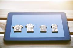 Symboles en bois des maisons sur la tablette numérique photos stock