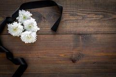 Symboles funèbres Fleur blanche près de ruban noir sur l'espace en bois foncé de copie de vue supérieure de fond photo stock