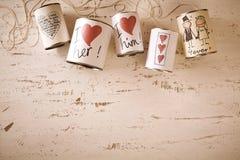 Symboles tirés par la main d'amour et de mariage sur des boîtes en métal Photo stock