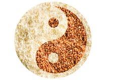 Symbolet av yin yang läggas ut ur bovete och ris, textur royaltyfri bild