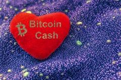 Symbolet för cryptocurrencyBitcoin kassa är en röd flott hjärta med en neonbakgrund BCH royaltyfri bild