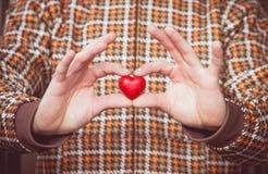 Symbolet för hjärtaformförälskelse i man räcker valentindag Arkivbild