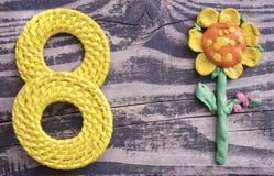 8 symbolet för mars och handgjord plasticine blommar på träbakgrund Lycklig design för dag för kvinna` s Kan användas som en deko Arkivfoto