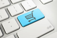 Symbolet för shoppingvagnen på blått knäppas tangenten av det vita tangentbordet, online-shopping Royaltyfria Bilder