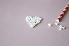 Symbolhjärta från preventivpillerrosa färgbakgrund Arkivfoto