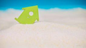 Symbolhus som byggs på sand, litet grönt symbol av ett hus som sjunker in i sanden royaltyfria bilder