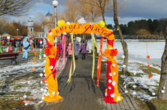 Symbolic arch of colorful cloth with inscription Gates of happin. GOMEL, BELARUS - FEBRUARY 25, 2017: Unidentified people visit Shrovetide festivities. Symbolic Royalty Free Stock Photo