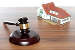 Symbolic auctioneer. With gavel and house model Stock Photos